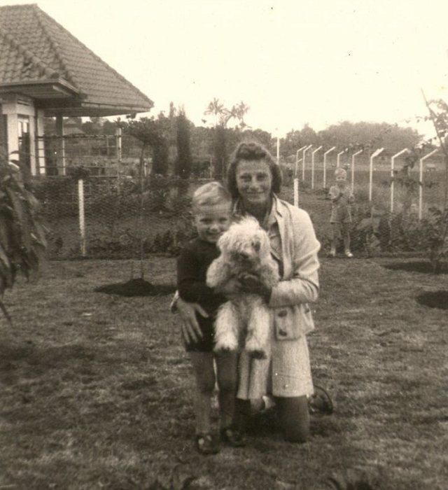Vrouw met kind en hond in de tuin