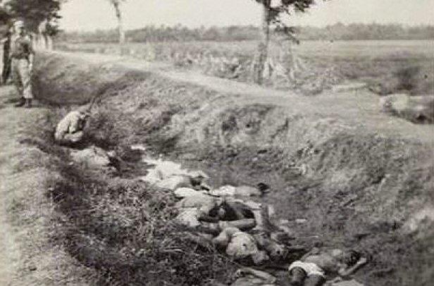 Foto (detail) uit album van Jacobus Ridderhof, waarop gedode Indonesiërs in greppel. De heer Nouwen meent zichzelf te herkennen in de hurkende persoon, linksboven.