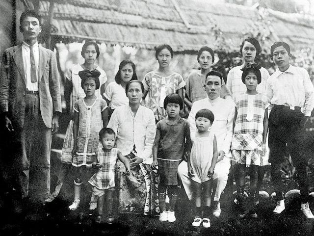 Opa Sim Thian Tik en oma Kwik Kwan Nio en hun twaalf kinderen, in Poerwokerto. Tante Hetty, in donkere jurk, tussen opa en oma. King, de moeder van de schrijfster, achter oma.
