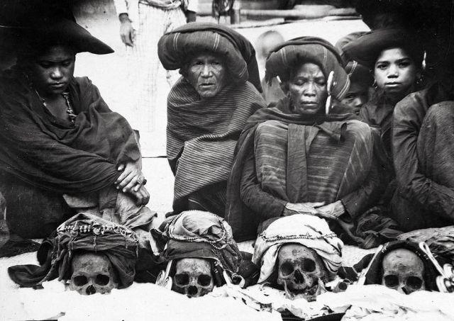 Groepsportret familie van Sibayak Pa Mbelgah in Kabandjahe met de schedels van hun voorouders voor zich (TM)